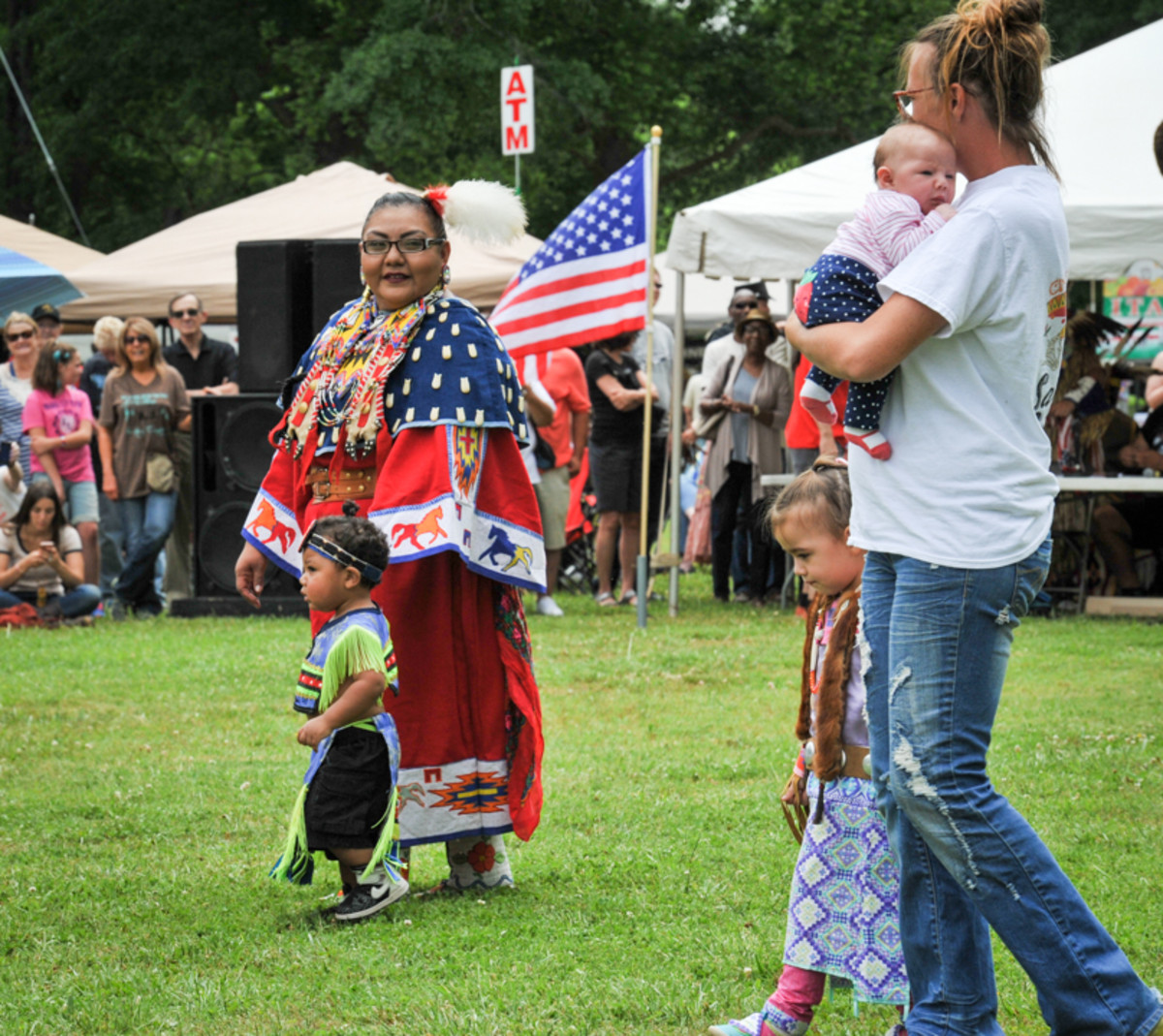 Tiny tots dance in the arena guided by their mothers at the Mother's Day Pow Wow in Canton, GA