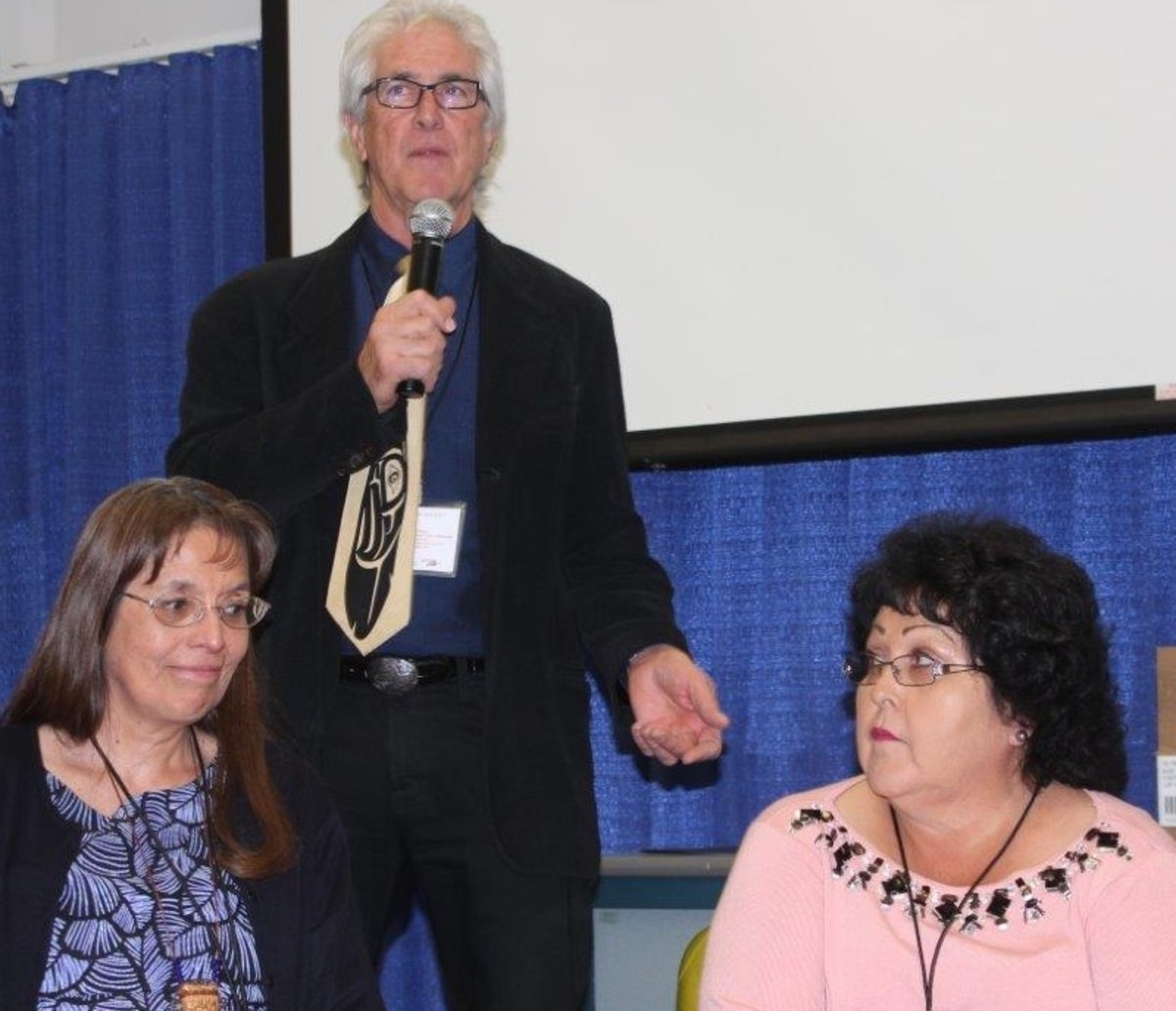 """""""Who Belongs?"""" conference organizer Robert Hershey introduces panelists at a tribal leaders Forum about tribal disenrollment. Chairwoman Carol Evans, Spokane Tribe of Indians, is on the left, and President Bernadine Burnette, Fort McDowell Yavapai Nation, is on the right."""