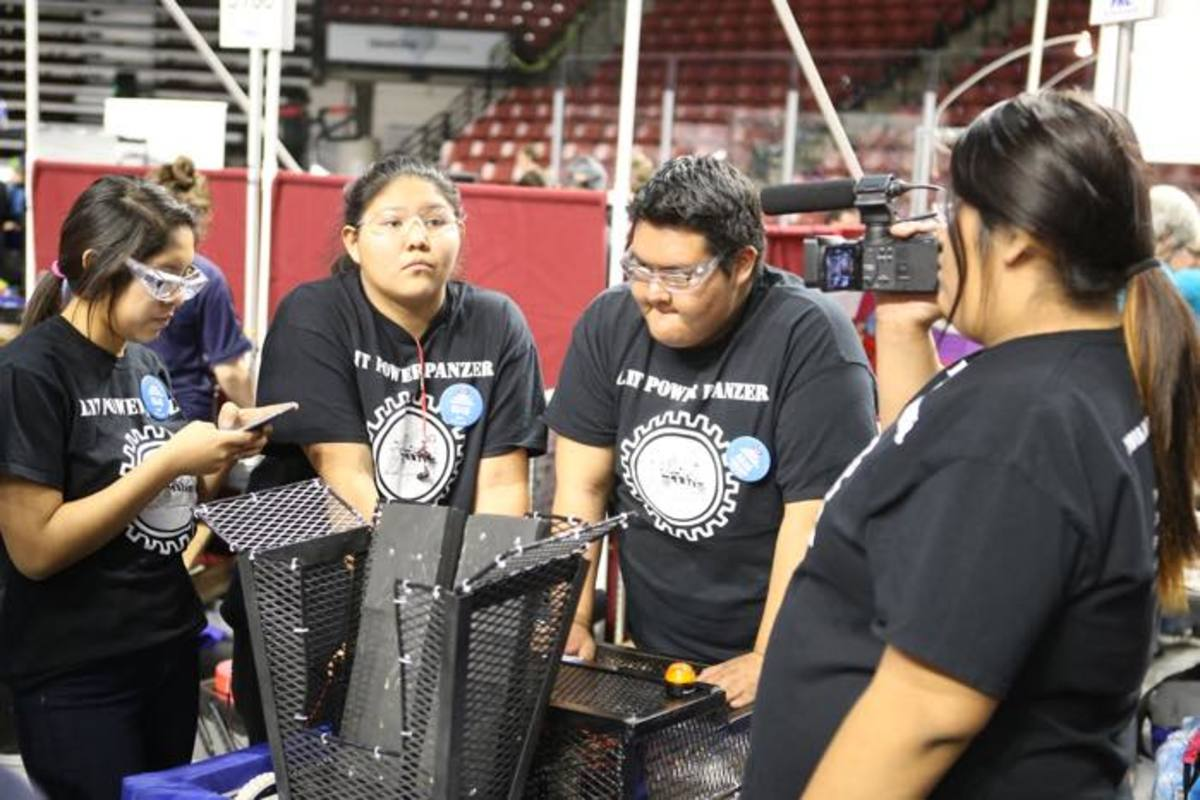 Native American students of Team 6546 Naatsis'áán troubleshoot during the Utah Regional FIRST Robotics Competition.