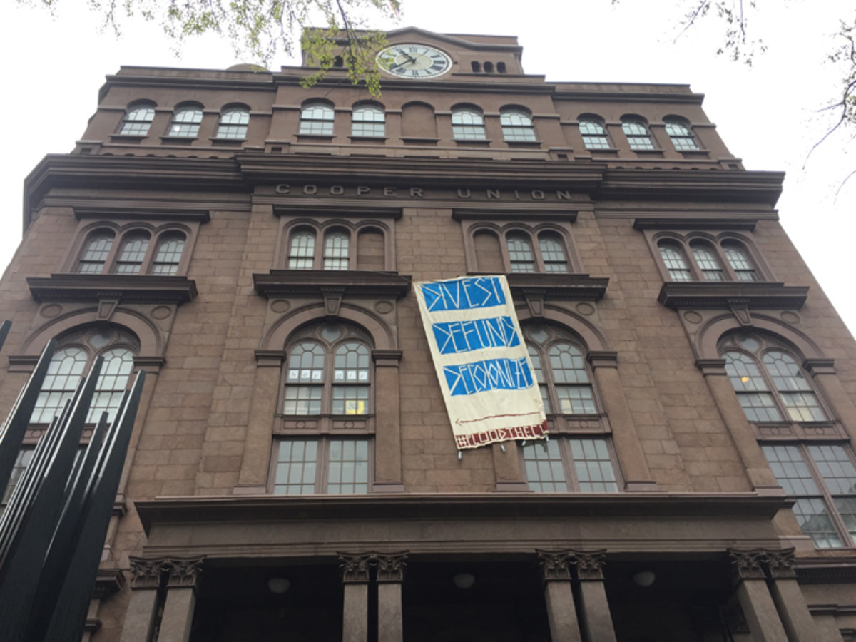 """""""Divest, Defund, Decolonize"""" banner was hung out the window of the Cooper Union Square Building in protest of Citibank's funding of pipelines."""