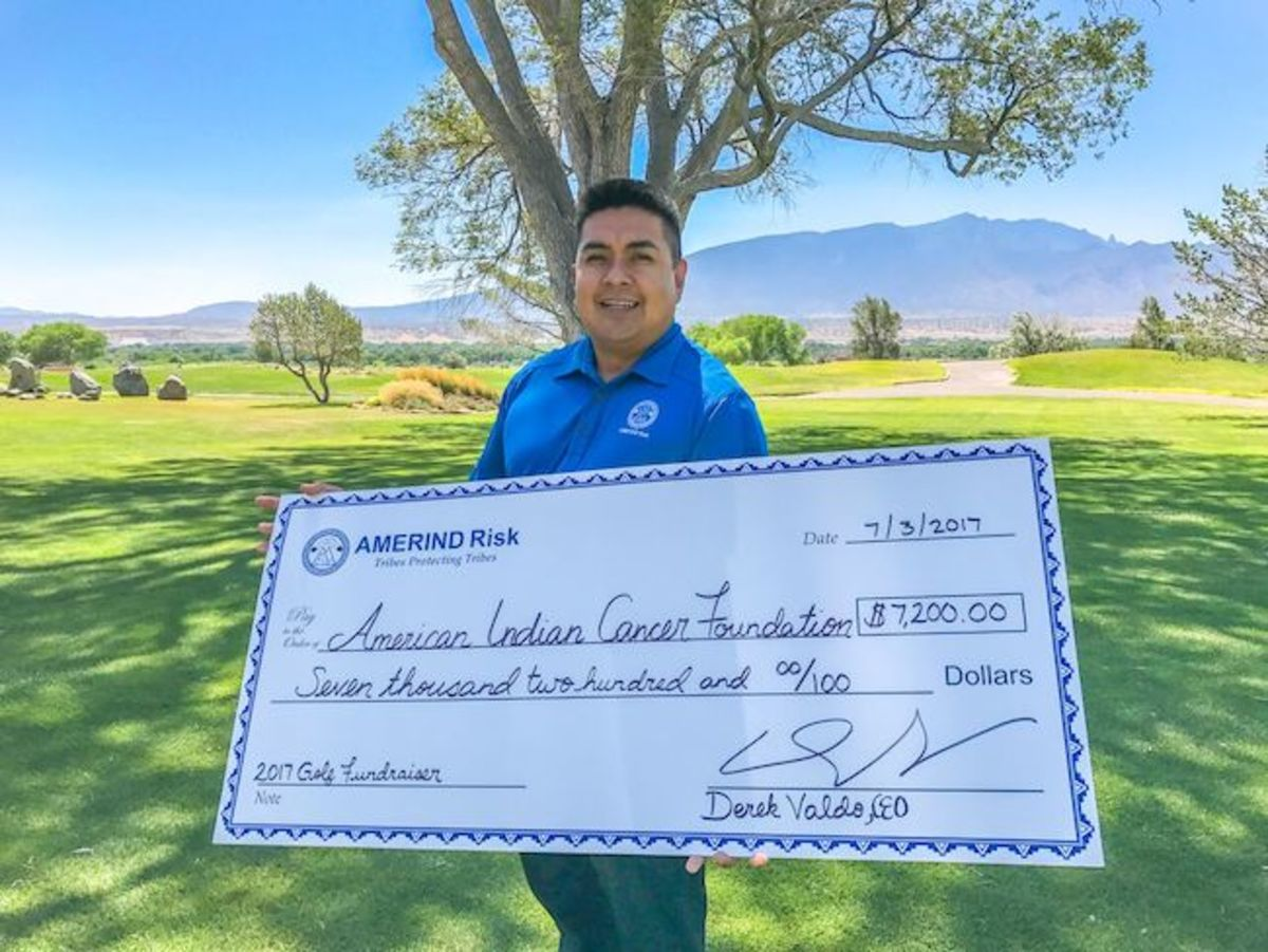 Derek Valdo (Acoma Pueblo), AMERIND Risk CEO, holds the donation check for $7,200 to the American Indian Cancer Foundation (AICAF).