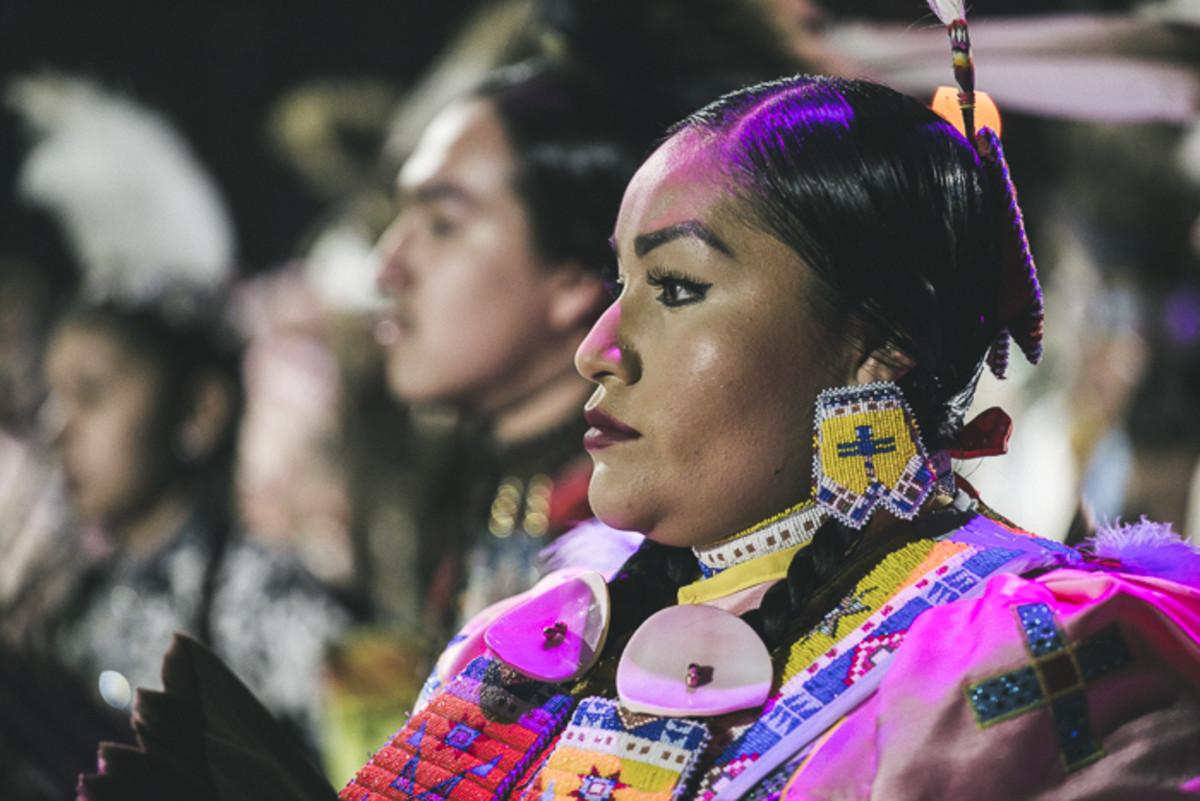 A woman looks on at the marvel of Grand Entry while she prepares to dance. Thosh Collins