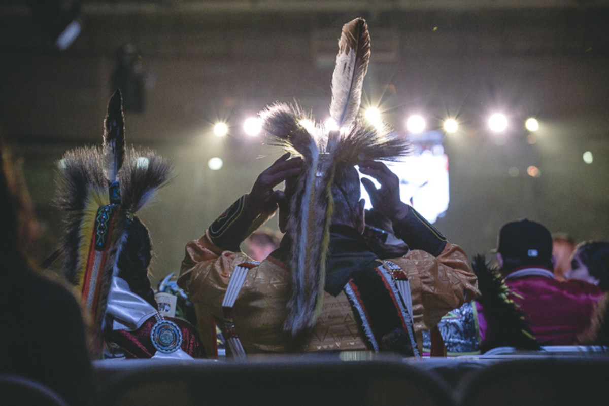 A dancer secures his roach while preparing for Gathering of Nations' Grand Entry. Thosh Collins