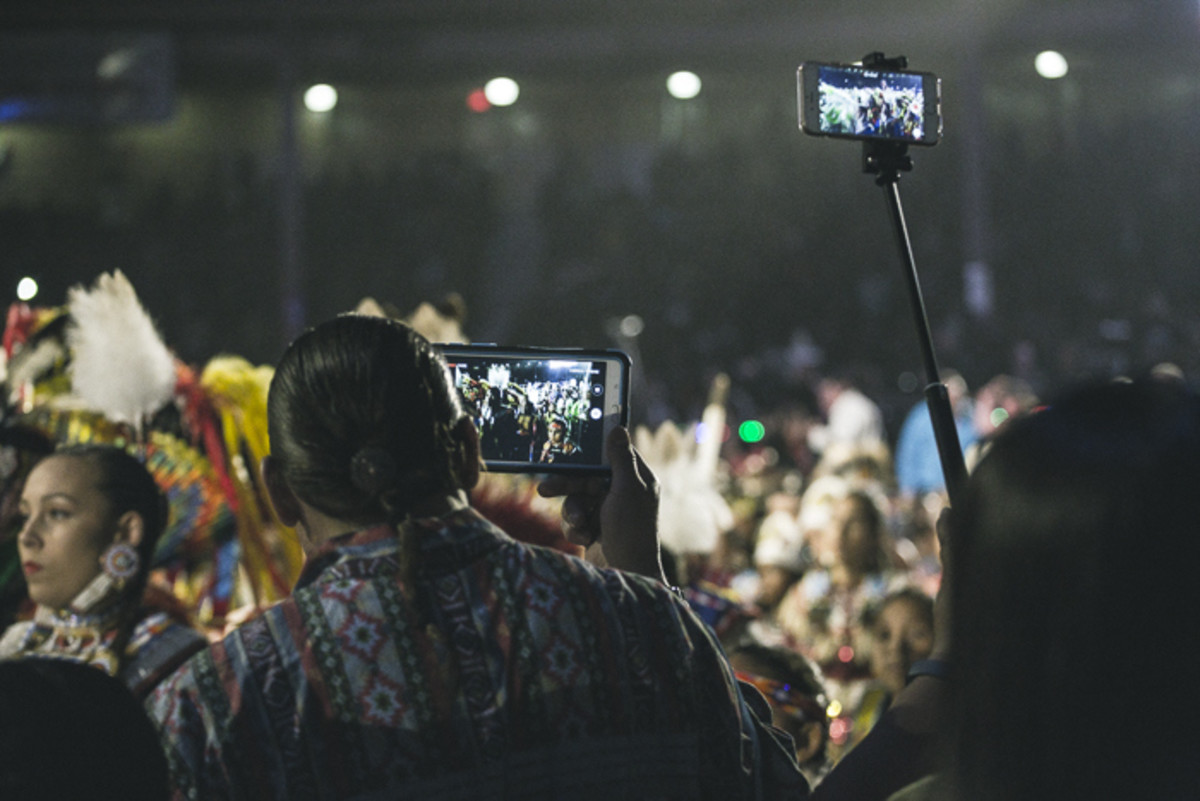 Thousands of recording devices from iPhones to iPads lit up the crowd while onlookers and participants alike seek to capture the beauty of the Gathering of Nations pow wow. Thosh Collins
