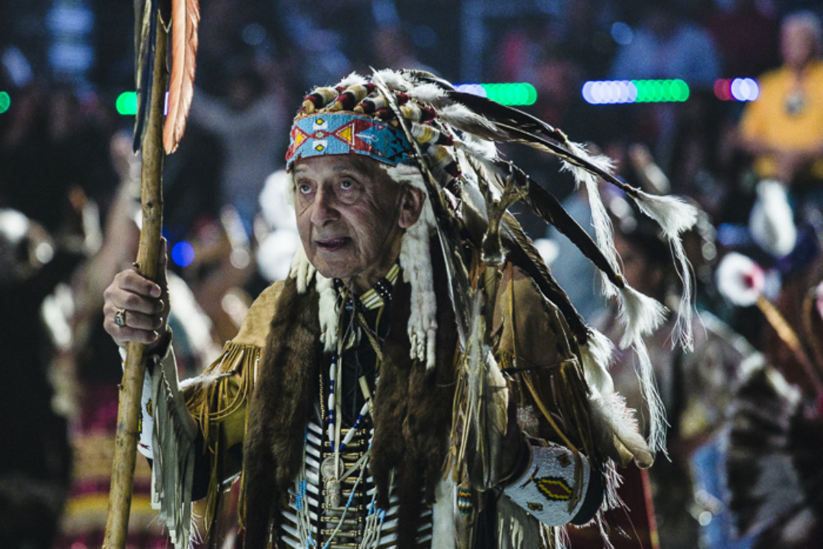An elder dances with a staff and headdress - signs of having earned honor and respect over the course of his life - during the Gathering of Nations Grand Entry on Saturday evening. Thosh Collins
