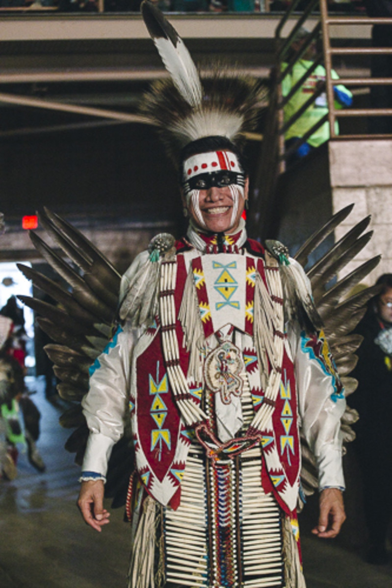 Ardell Scalplock from Siksika, Alberta stops to smile for a photo while walking the floor just before Friday evening's Gathering of nations' Grand Entry. Thosh Collins