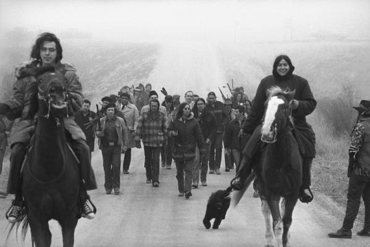 Harlington Wood, Assistant U.S. Attorney General, third row center without hat, is escorted into Wounded Knee by Indians of the AIM on March 13, 1973. Second row, left, is Russell Means, one of the AIM leaders and Carter Camp, another leader walks beside Wood. Wood was sent to the reservation in an effort to find a solution to the problem.