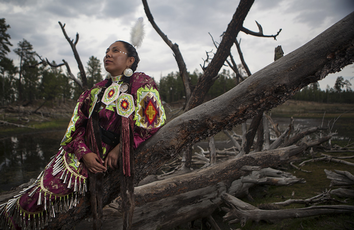 Jingle dress dancer Mikka Cree Walters at the banks of a small lake in the Chuska Mountains. Diego James Robles