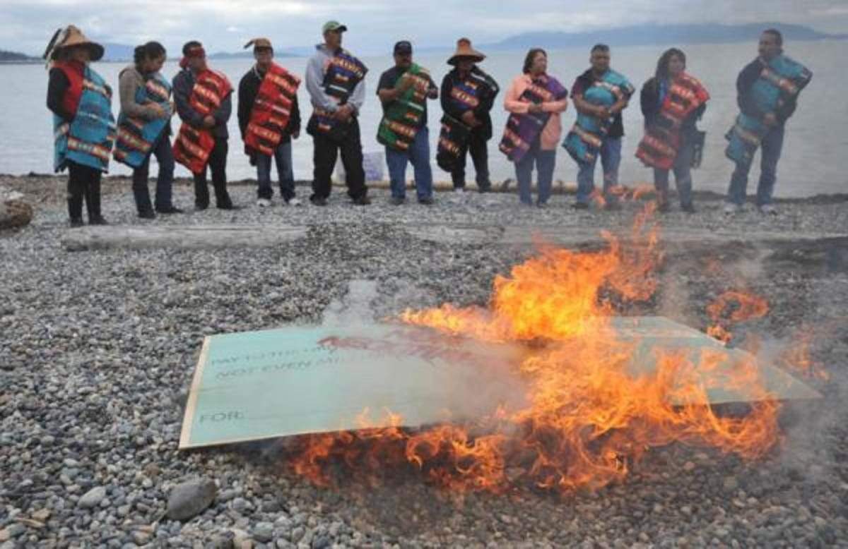 """Members of the Lummi Nation protest the proposed coal export terminal at Cherry Point by burning a large check stamped """"Non-Negotiable."""" The tribe says they want to protect the natural and cultural heritage of the site."""
