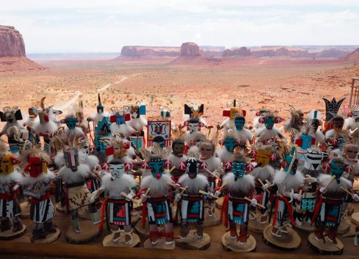 Traditional hand-crafted Native American figures displayed for sale at a souvenir shop at Monument Valley Navajo Tribal Park. Visible in the back are the valley's famous red rock formations.