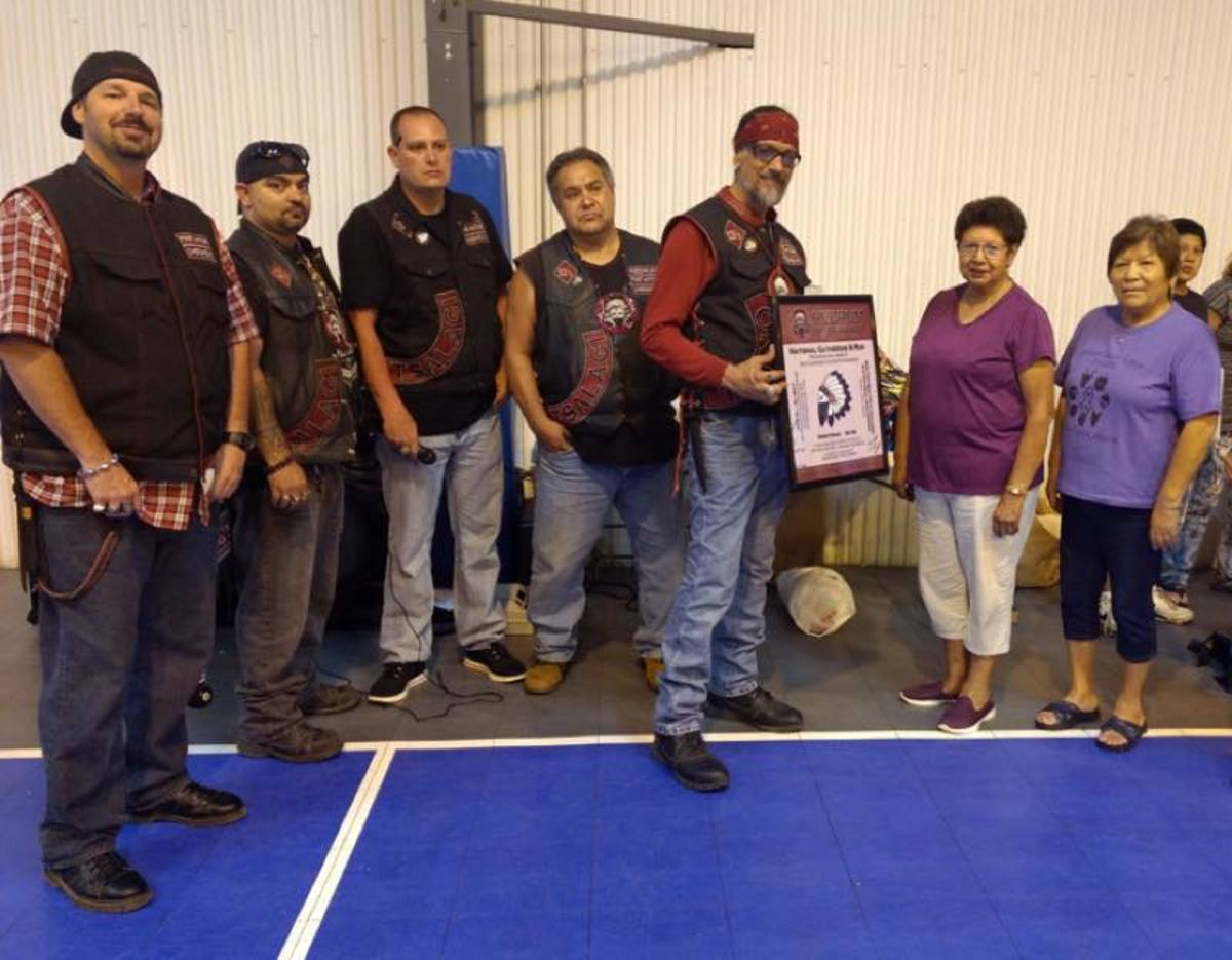 Cherokee Redrum members give a $5,000 donation to the Cancer Support Fund.