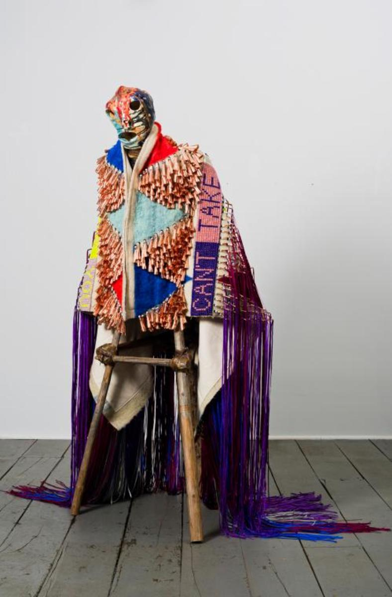 """Jeffrey Gibson - Mississippi Band Choctaw - Cherokee """"Can't Take My Eyes Off You."""" High fire glazed ceramic, repurposed tipi poles, wool, acrylic paint, wool blanket, glass beads, artificial sinew, copper jingles, and nylon fringe; 72 x 29 x 38 in. Collection of Vicki and Kent Logan. Image courtesy of Jeffrey Gibson Studio and Roberts & Tilton, Los Angeles, California. Photograph by Peter Mauney."""