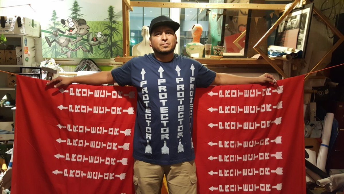 Dine' artist and activist Remy at his studio in Washington DC standing amidst Protector sashes worn at NoDAPL rallys - Photo Vincent Schilling