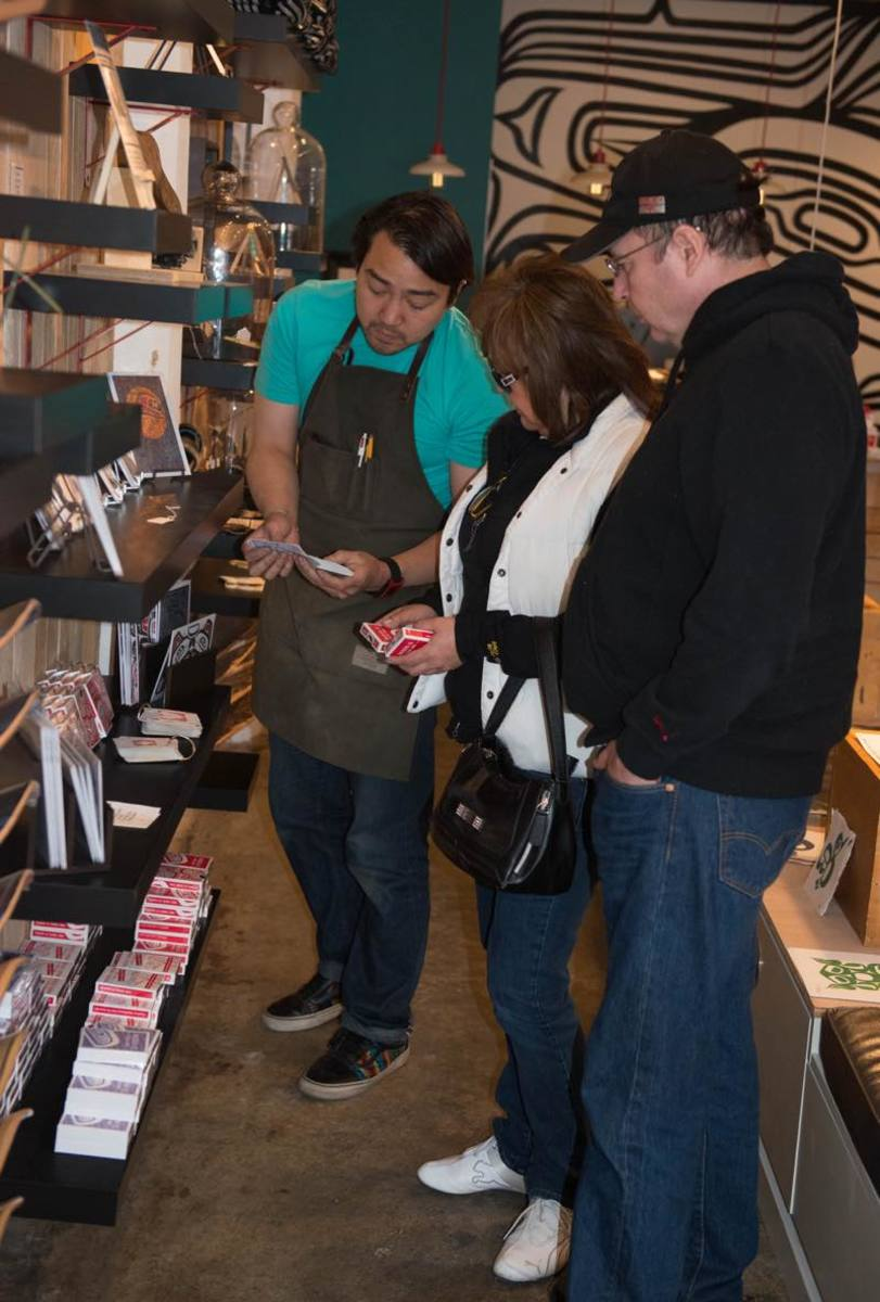 Rico Worl welcomes guests Darlene Smith of Whitehorse and Wayne Chambers of Haines to his store. Smith took an interest in playing cards with designs reflecting Worl's Tlingit heritage.