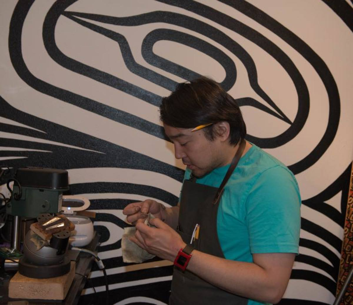 Tlingit Artist Rico Worl attaches an earring loop to a piece of silver with a baleen engraving.