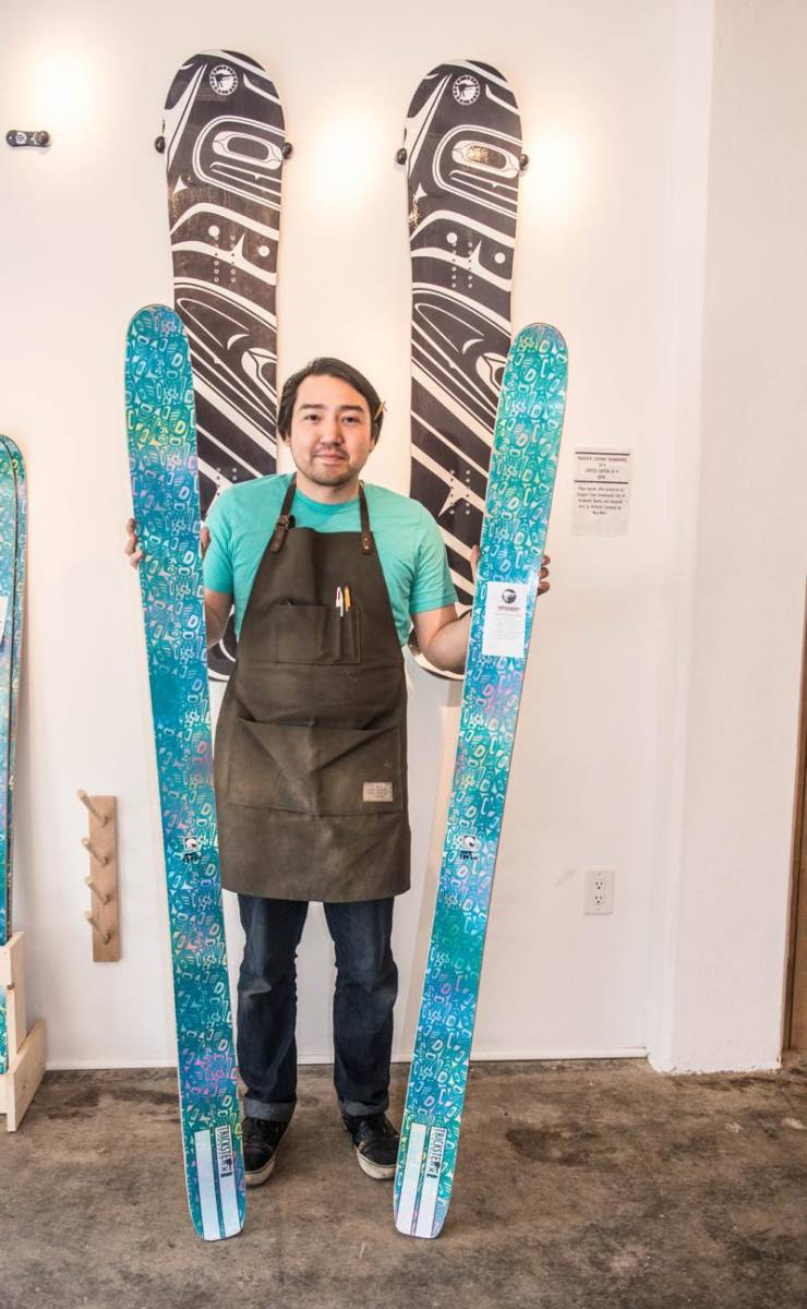Tlingit artist Rico Worl stands with a pair of skis and snowboards bearing his designs.