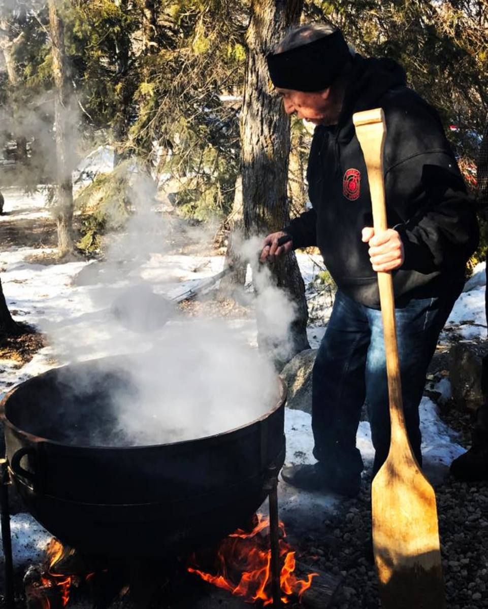 George Martin of Gun Lake Pottowatomi in Michigan, prepares traditional flint corn into hominy corn over an outdoor hearth at the Indigenous Farming Conference in White Earth Ojibwe territory. Teaching Native American youth about food sovereignty is important.