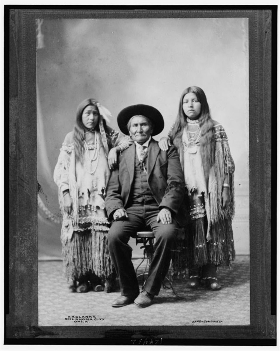 Geronimo, seated, with his two nieces standing at his sides, circa 1900-1909.