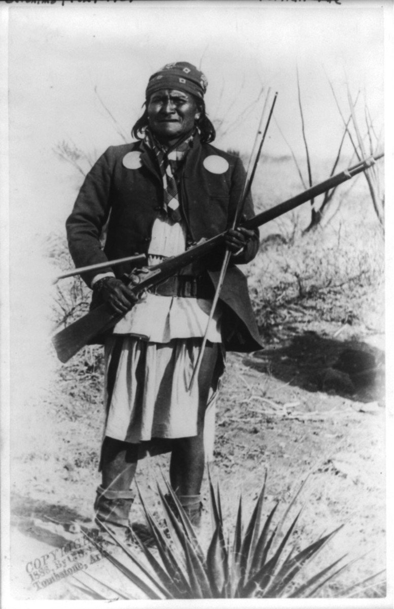 Scene in Geronimo's camp, March 25th-26th, before surrender to General Crook on March 27, 1886. Geronimo, full-length portrait, rifle at port. Photo by C.S. Fly. Fly's photographs are the only known images of Indian combatants still in the field who had not yet surrendered to the United States.