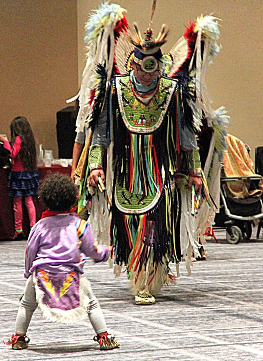 A tiny-tot dancer has hopes of being like this male fancy dancer someday.