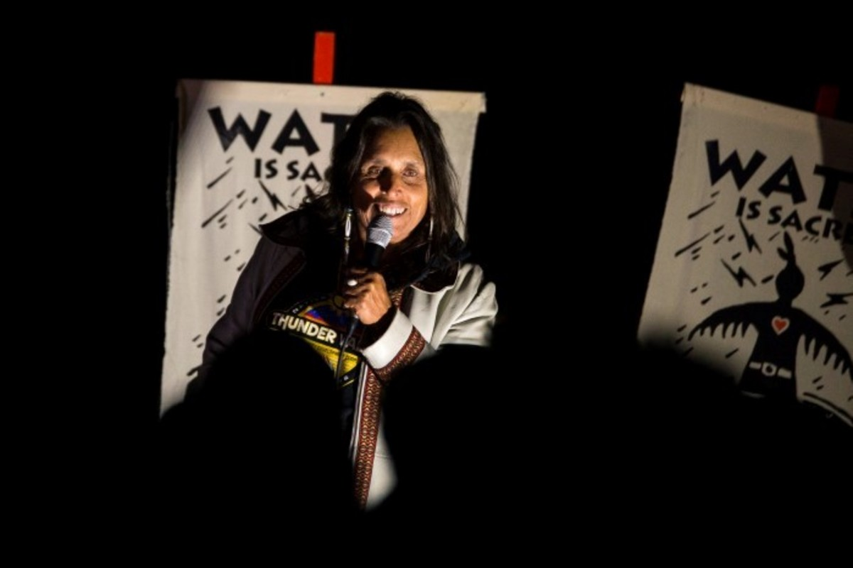 Winona LaDuke introducing Nahko Bear at a nighttime concert at the Oceti Sakowin camp - Photo Alex Hamer