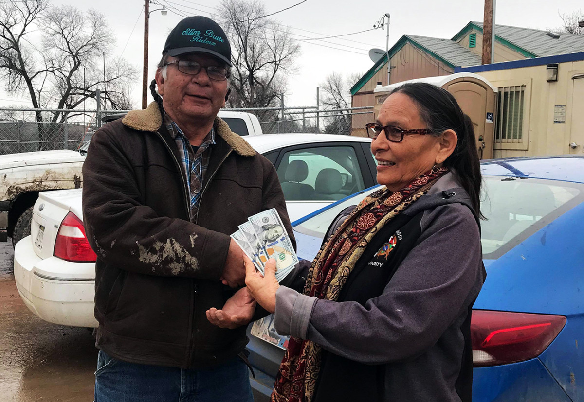 Pine Ridge resident Saunie Wilson hands Marvin Goings a donation, enabling the delivery of 6 truckloads of supplies to outlying district.