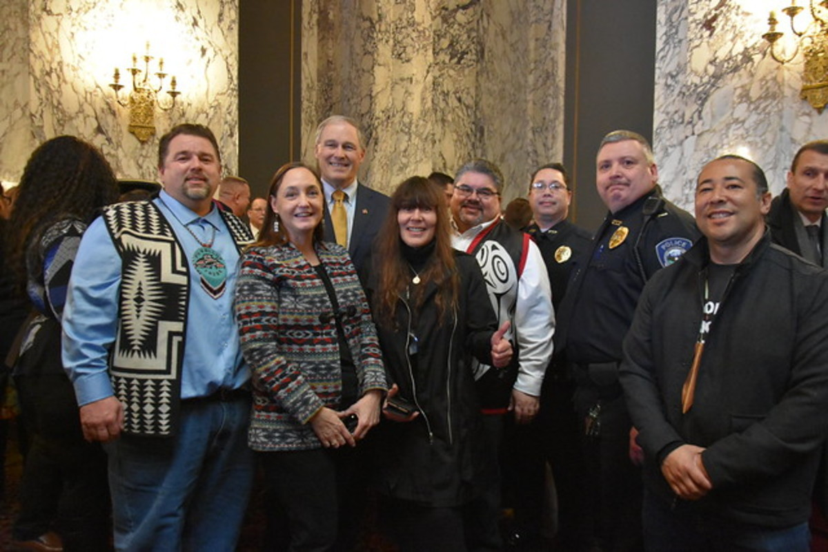 Puyallup tribal members stand with Gov. Jay Inslee on February 4, 2019 at the signing of Substitute House Bill 1064, the modified police de-escalation bill. From the left, Chester Earl, Annette Bryan, Gov. Inslee, Lisa Earl, Tim Reynon, William Losier, Jeff Berys Sr., David Bean (Photo courtesy Governor Inslee's office)