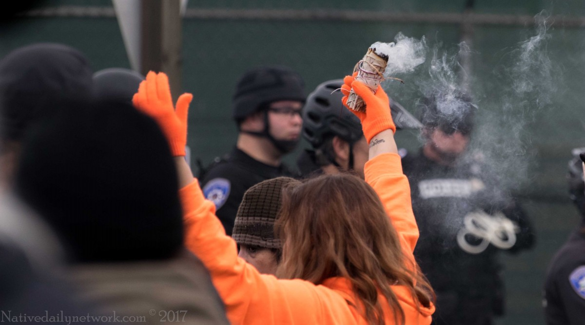 As Tacoma Police in riot gear look on, a Puyallup Tribal ally burns sage. Photo taken at the 'Block the Gates' direct action event outside the construction site of Puget Sound Energy's plant in Tacoma, December 18, 2017 (Photo Courtesy Darren Moore/NativeDailyNetwork.com)
