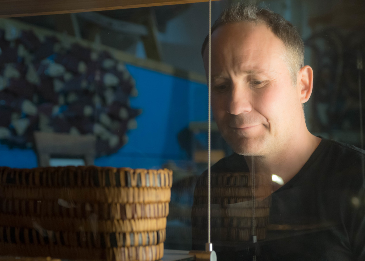 Spirit Works owner Shain Jackson peers at his late grandmother's traditional hand-woven baskets inside a display case at his studio in North Vancouver.