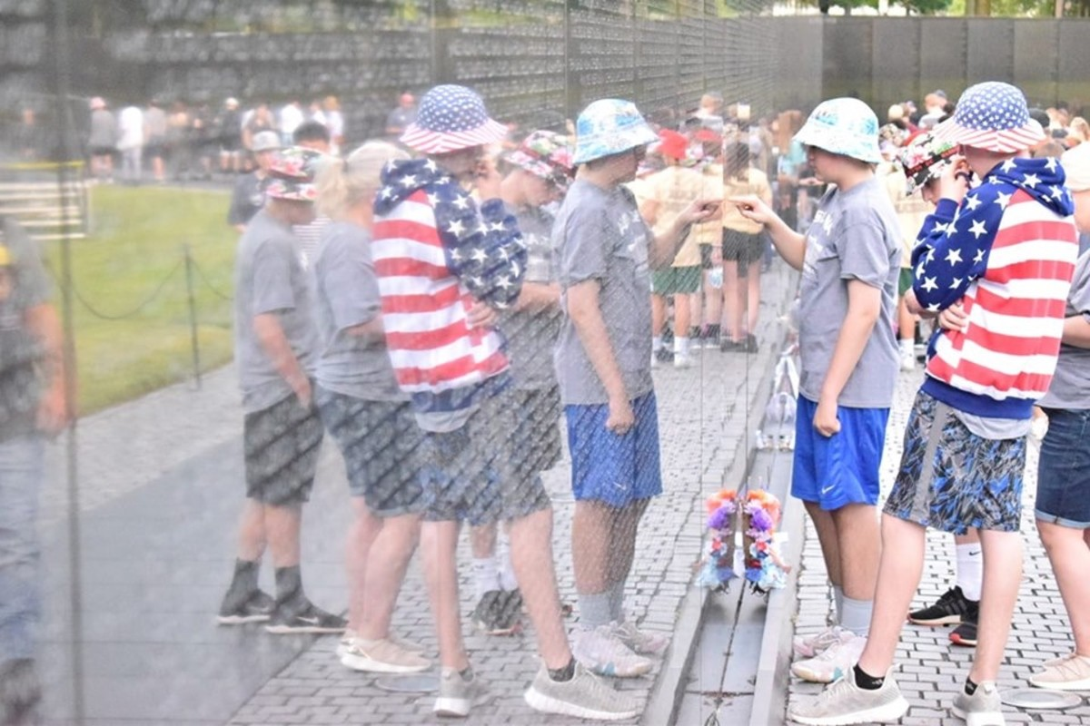 Students examine the names of fallen soldiers at the Vietnam Veterans Memorial Wall.