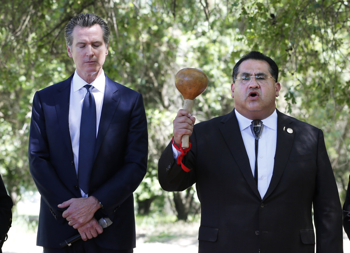 Gov. Gavin Newsom, left, bows his head as Assemblyman James Ramos, D-Highlands, of the San Manuel Band of Mission Indians, opens a meeting with tribal leaders from around the state at the future site of the California Indian Heritage Center in West Sacramento, Calif., Tuesday, June 18, 2019. Newsom took the occasion to formally apologize to tribal leaders from around California for the violence, mistreatment and neglect inflicted on Native Americans throughout the state's history. (AP Photo/Rich Pedroncelli, File)