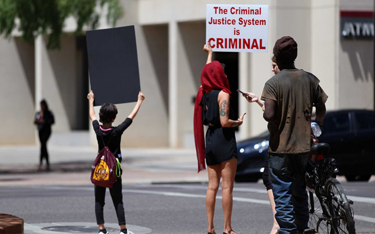 """Leslie Pico, 32, and her daughter Elisa, 9, of Phoenix, hold signs outside City Hall. As a """"white-passing first-generation Latina,"""" Pico says, it's important to volunteer and raise the platform of such organizations as Poder in Action and Black Lives Matter. (Photo by Tanner Puckett/Cronkite News)"""