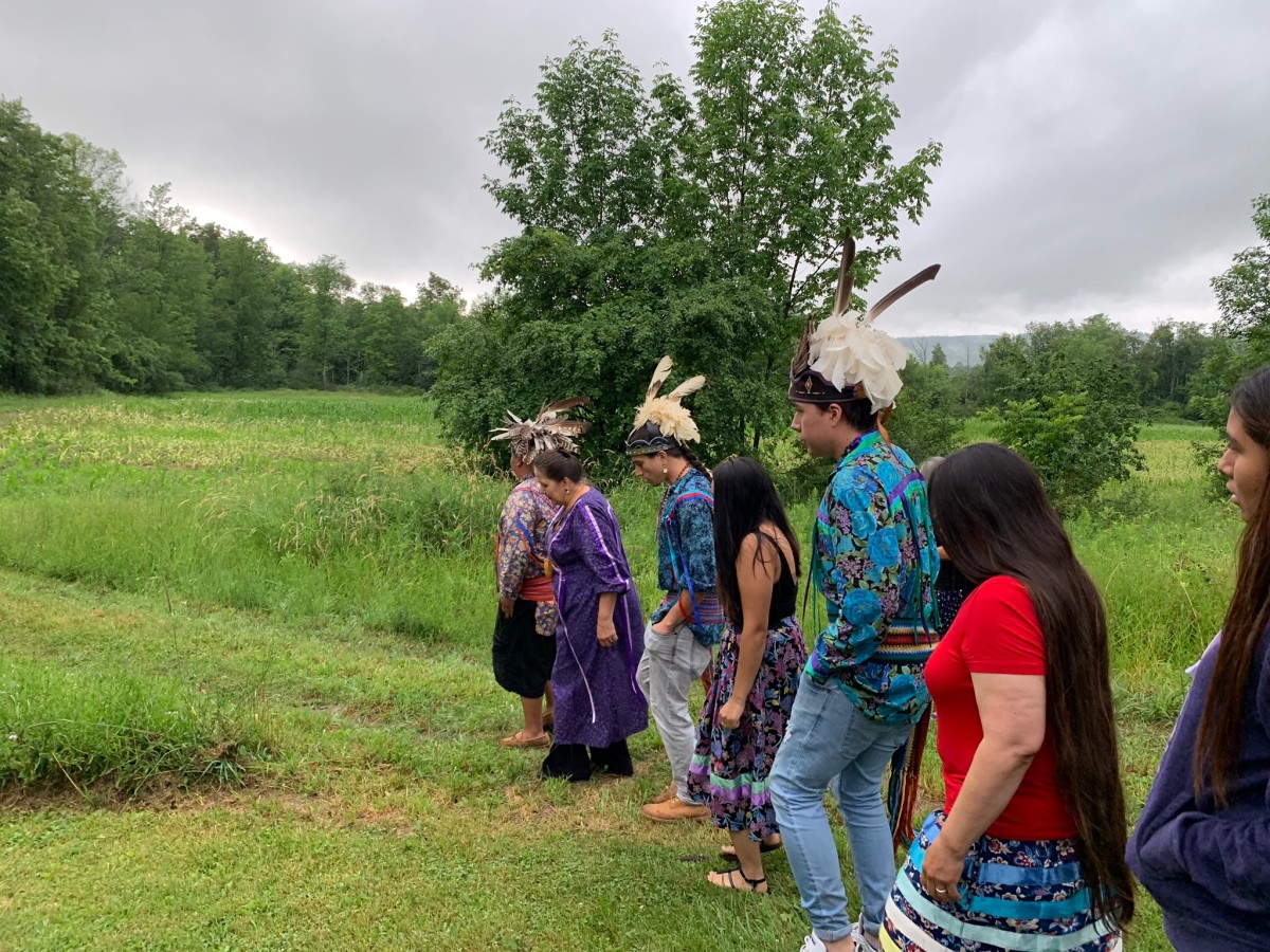Three Oneida men lead a stomp dance. The land that has been returned is just behind the picture. (Photo by Michelle Schenandoah)