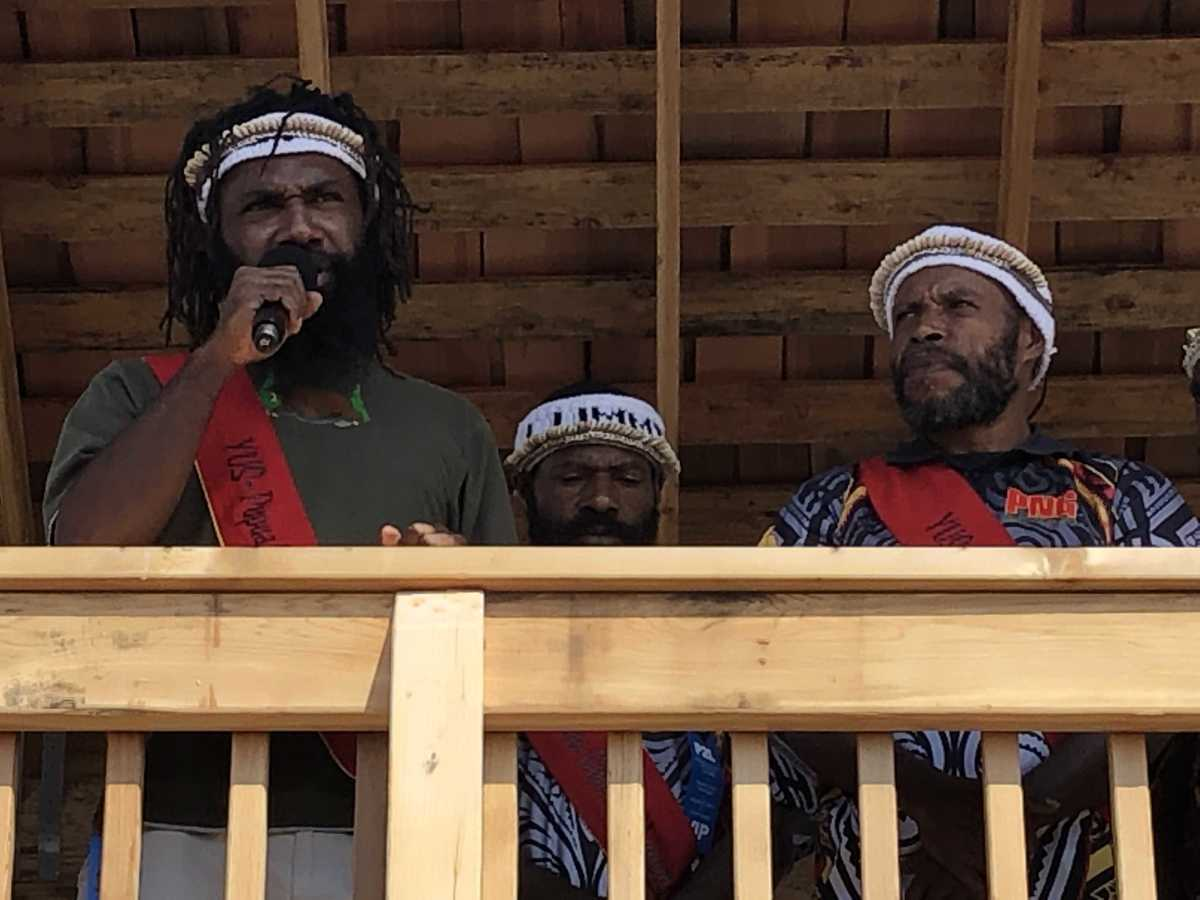 A representative of the Papuan delegation from New Guinea speaks to the crowd July 24 at the landing site on Lummi Nation's shores. He said the Papuan people stand as one with Lummi in Lummi Nation's efforts to protect the environment and defend sovereignty.