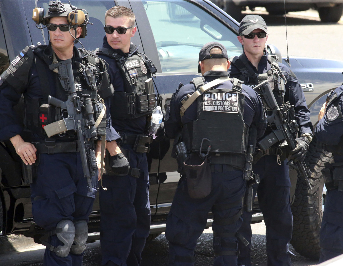U.S. Customs and Border Protection officers gather near the scene of a shooting at a shopping mall in El Paso, Texas, on Saturday, Aug. 3, 2019. Multiple people were killed and one person was in custody after a shooter went on a rampage at a shopping mall, police in the Texas border town of El Paso said. (AP Photo/Rudy Gutierrez)