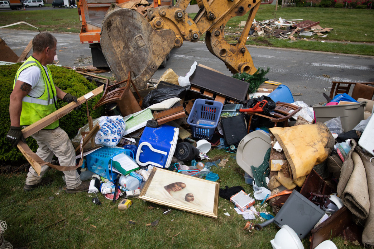 """Phil Sloan, a worker from adjacent Butler County, Ohio, sorts through ruined belongings that Dayton residents have set out for removal. """"I just feel bad. That's a lifetime of stuff laying out here in a pile,"""" Sloan said."""