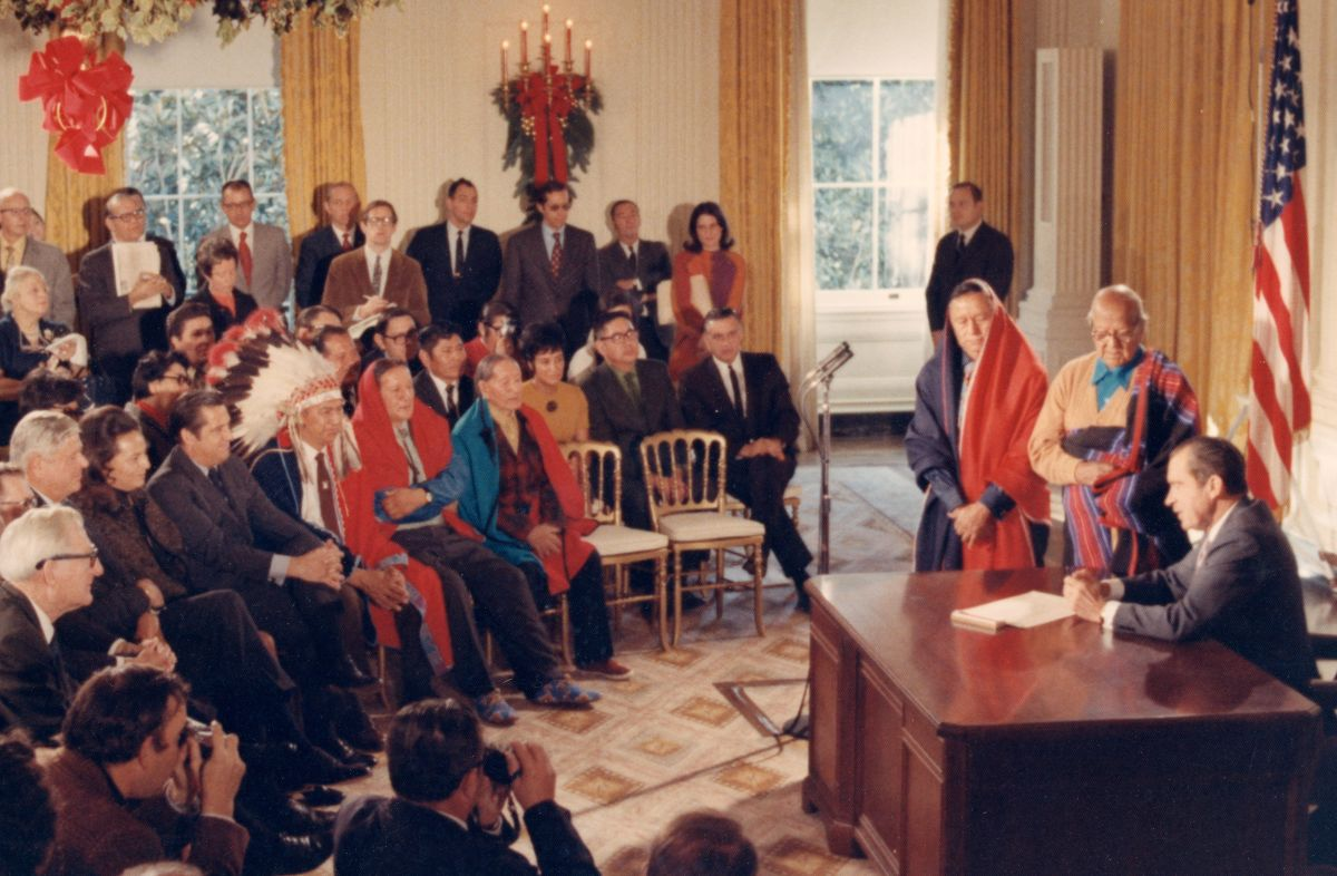 Fred and LaDonna Harris sit in the front row as President Nixon signs a bill returning Taos Blue Lake to Taos Pueblo. (Nixon Library)