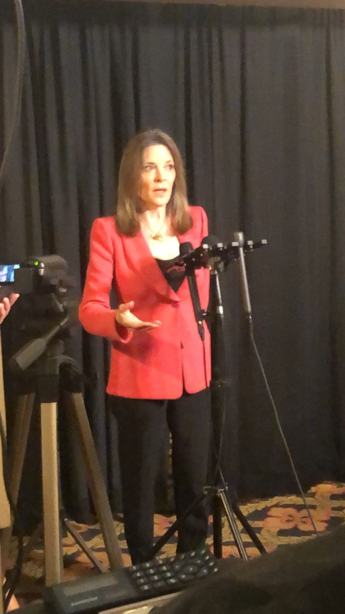 Author Marianne Williamson taking questions from the press in the media room.