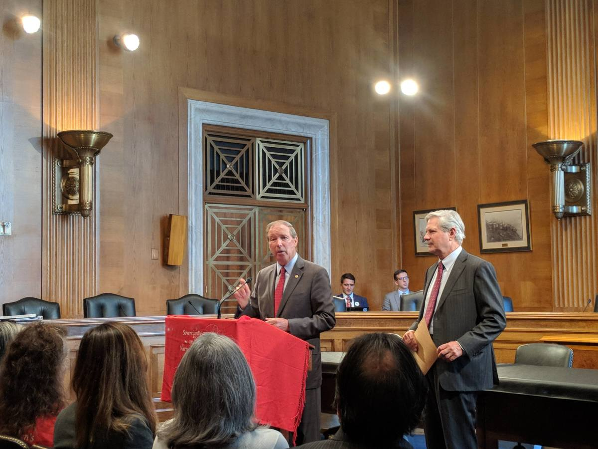 Sen. Tom Udall, left, and Sen. John Hoeven cracked a couple jokes and spoke of their bipartisan work while addressing tribal leaders (Photo by Kolby KickingWoman)