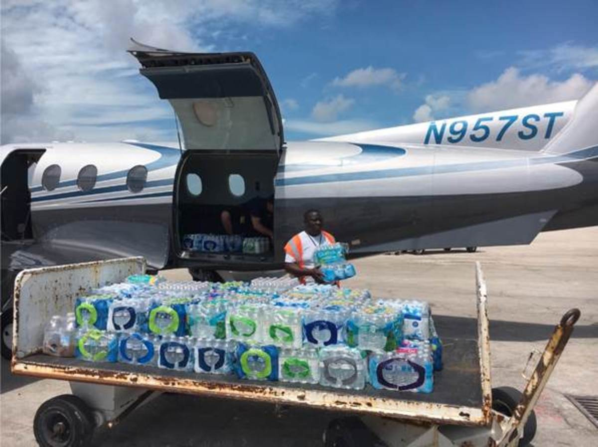 Pictured: An airport worker in Freeport on Grand Bahama Island helps to unload cases of bottled drinking water destined for victims of Hurricane Dorian from a Seminole Tribe of Florida Pilatus PC-12/45 single-engine aircraft.
