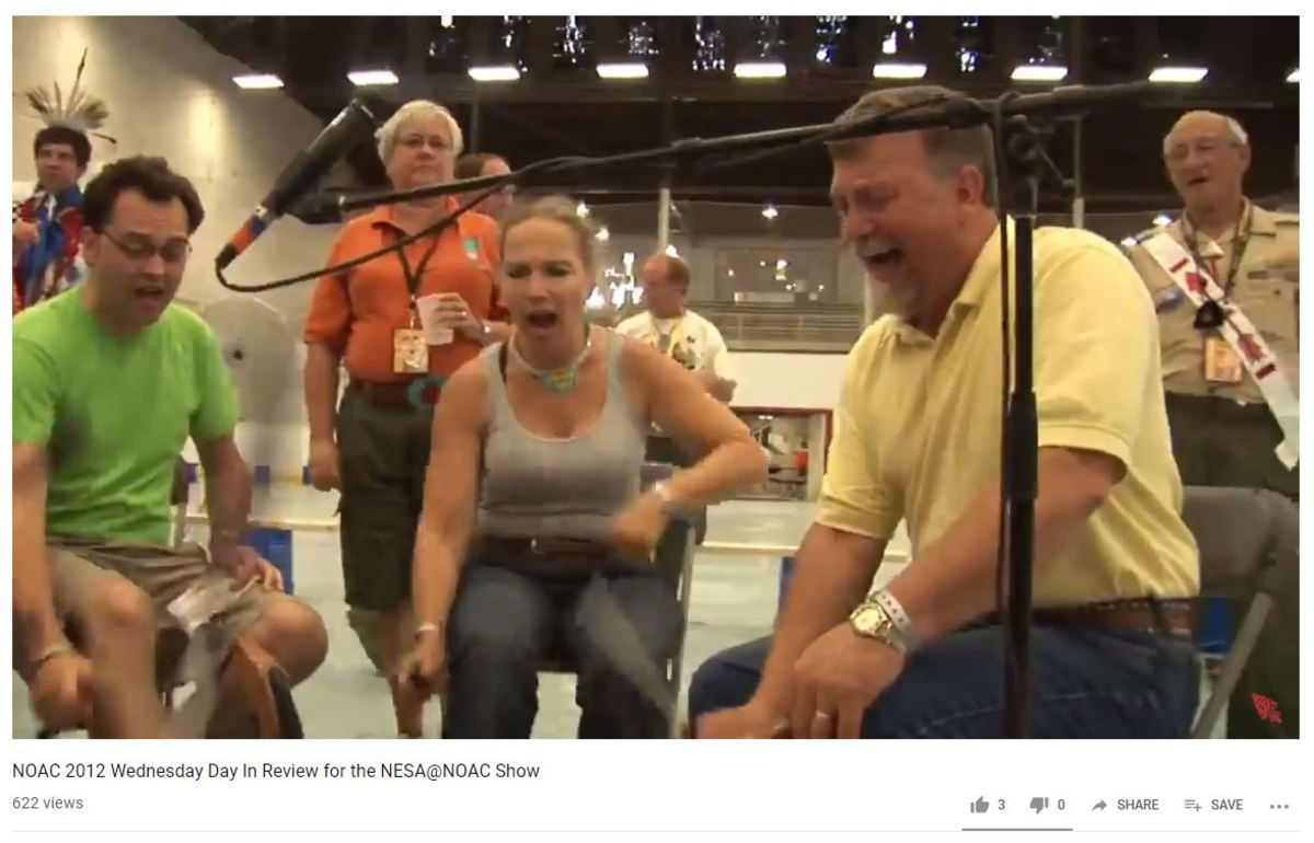 Order of the Arrow participants hitting a drum to create a song for dancers. Screen capture.
