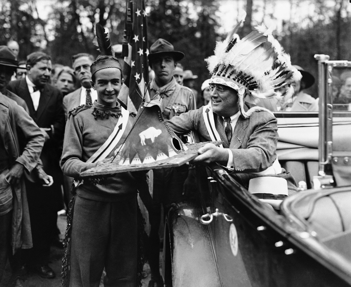 """President Franklin D. Roosevelt wears a Native American war bonnet when he was inducted into the National Scout Order of the Arrow, a """"brotherhood of service,"""" Aug. 23, 1933. He receives a miniature tepee as a gift from scout Robert Scott of Queens, N.Y., at Ten Mile River Camp, N.Y."""
