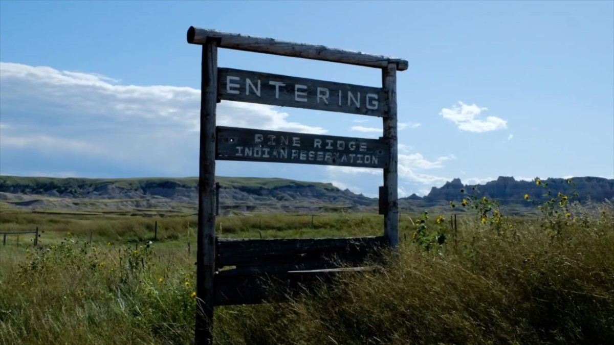 """Pictured: Oglala Sioux Tribe """"Entering Pine Ridge Indian Reservation"""" sign."""