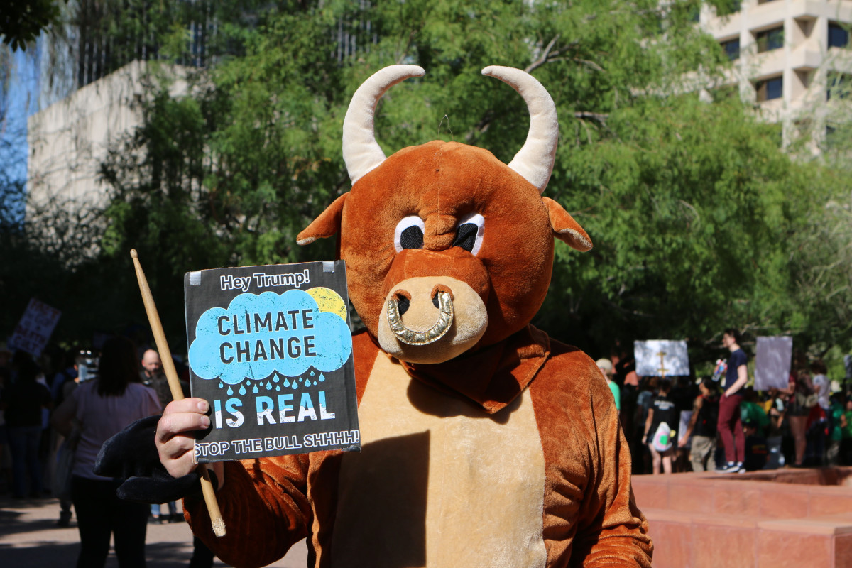 William Robles of Guadalupe, dressed as a bull, holds a sign asking President Donald Trump to recognize that climate change is not a hoax. (Photo by Annika Tomlin/Cronkite News)
