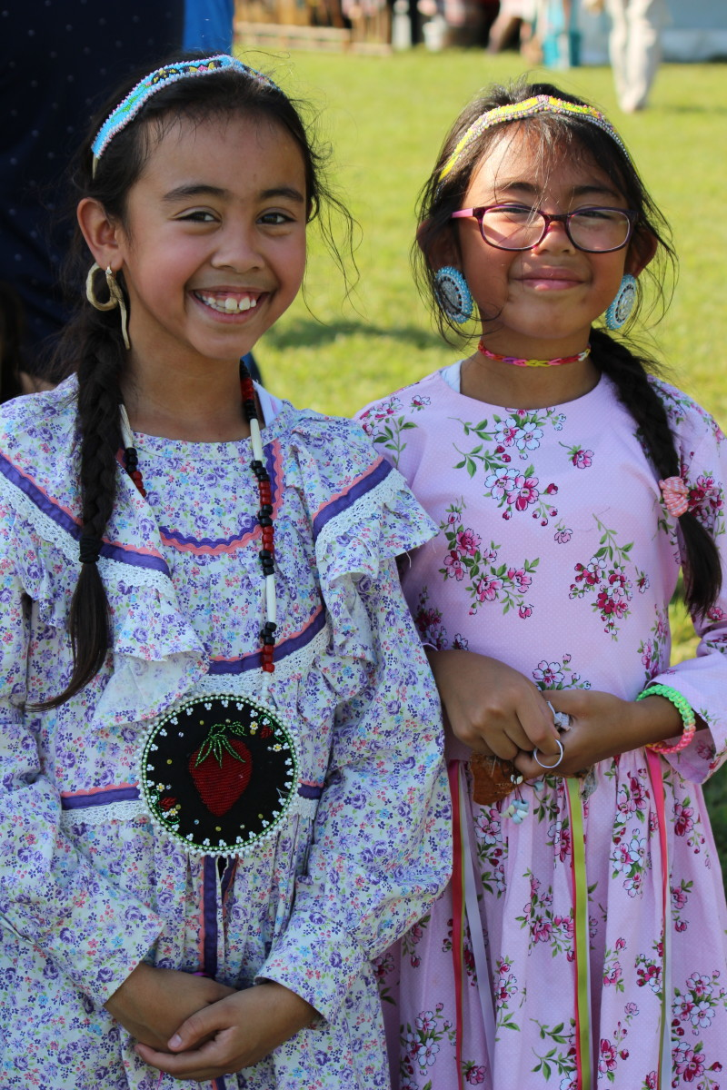 Sisters Aiyana and Brielle Suarez from the Meherrin Nation having a fun time at the powwow while showing gracious smiles. - Photo: Vincent Schilling