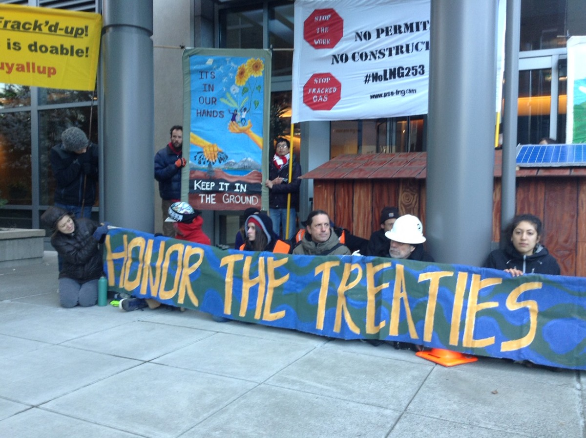 Members of 350 Tacoma, 350 Seattle, Redefine Tacoma, and the Puyallup Tribe use a replica of a Native American longhouse to block the entrance to the Bellevue offices of Puget Sound Energy on April 2, 2018. The direct action event was meant to raise awareness of the company's unpermitted construction of a liquified natural gas plant in the Puyallup River estuary. (Photo by Frank Hopper)