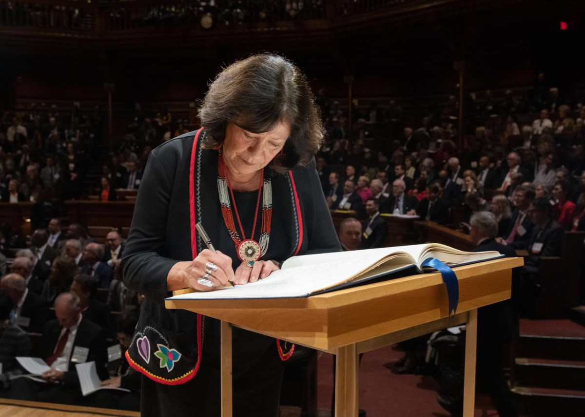 Patty Loew, Bad River, signs her name into the Academy's 'Book of Members,' a tradition tying back to the beginning of the Academy in 1780.