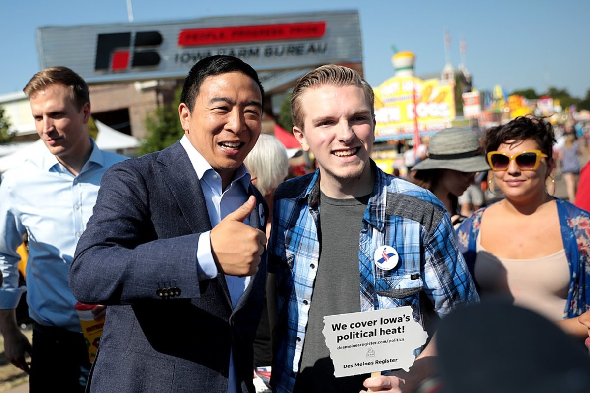 Pictured: Andrew Yang speaking with a supporter at the Des Moines Register's Political Soapbox at the 2019 Iowa State Fair in Des Moines, Iowa. Yang has generated a lot of enthusiasm among young people with his basic income plan.