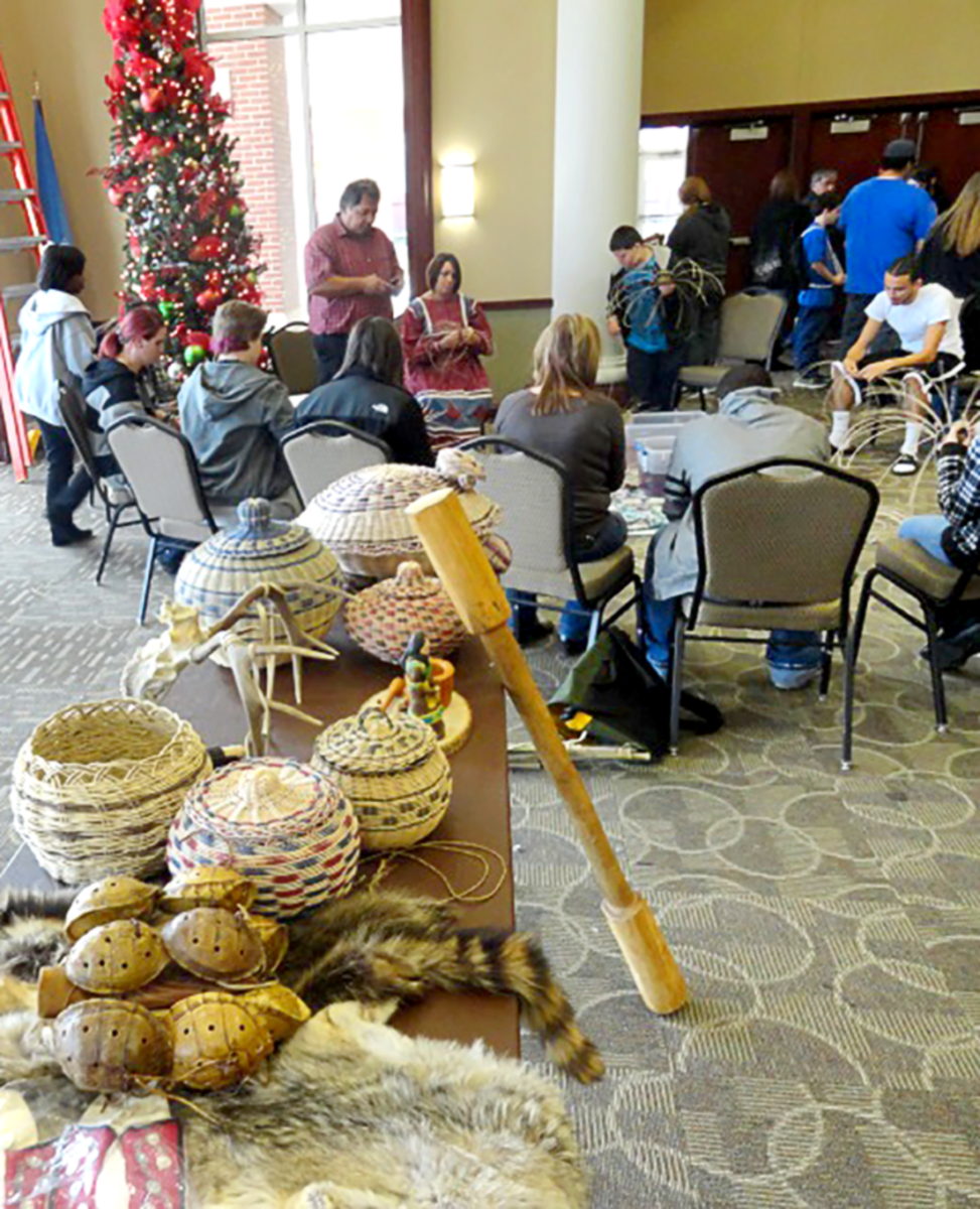 Pictured: A table of Native American baskets and attendees working on art projects in the background during a past Rogers State University Native American Festival.