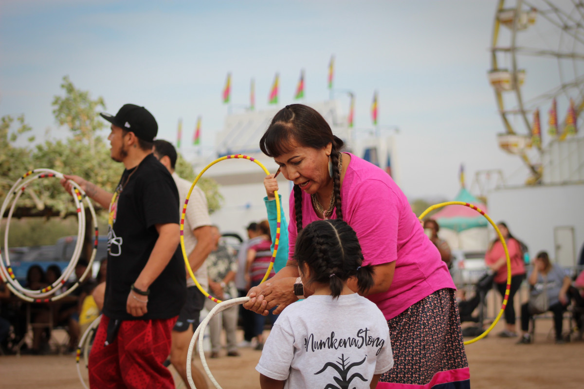 Doreen Duncan teaches a girl how to hoop dance during the community hoop dance. (Photo byQuindrea Yazzie)